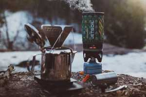 A pot steaming with a french press coffee maker resting on a log outdoors