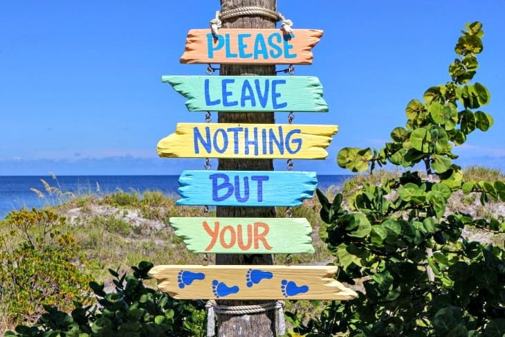 """sign that reads """"please leave nothing behind but your footprints"""""""