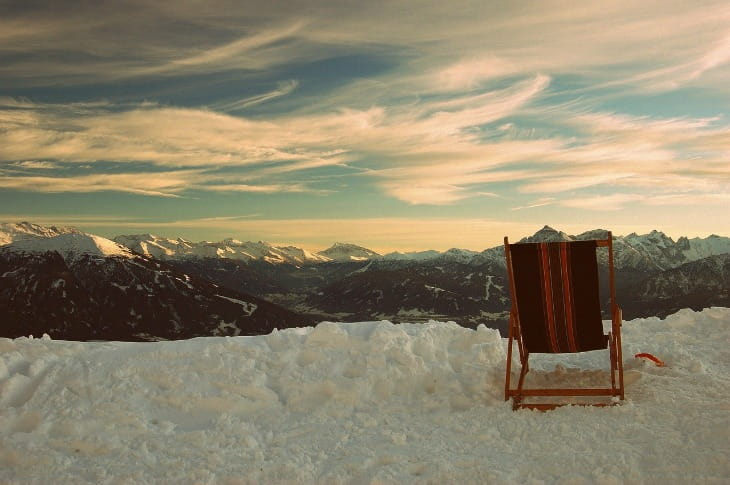 A chair sitting on the snow looking at the horizon