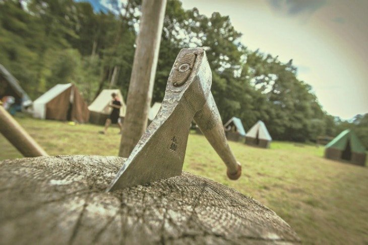 Hatchet stuck in a log at a campsite