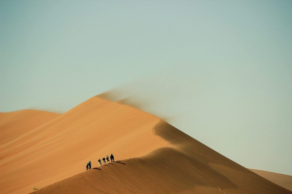 People hiking on the top of a sand dune
