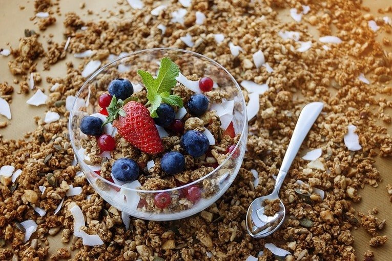 Bowl of granola with fruit on top.