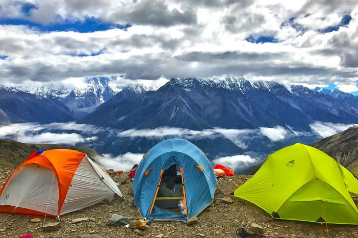 3 tents side by side overlooking a mountain range