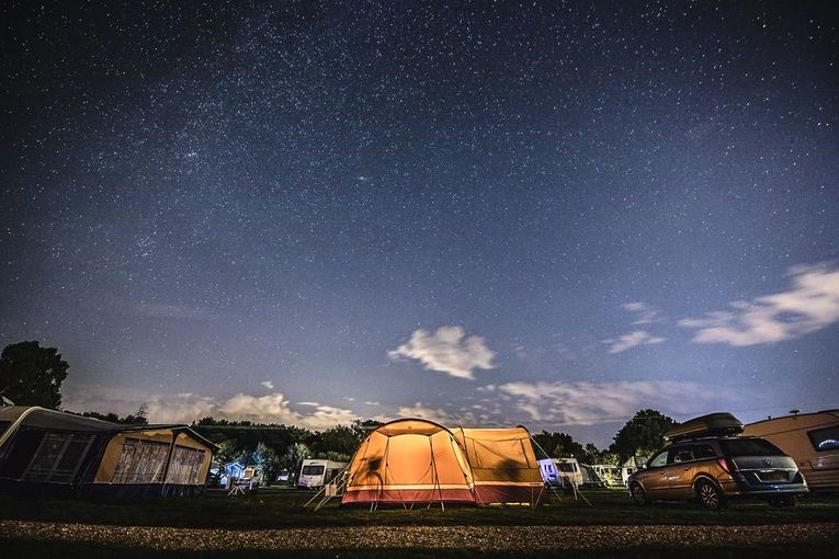 A large tent lit up at night under a starry sky