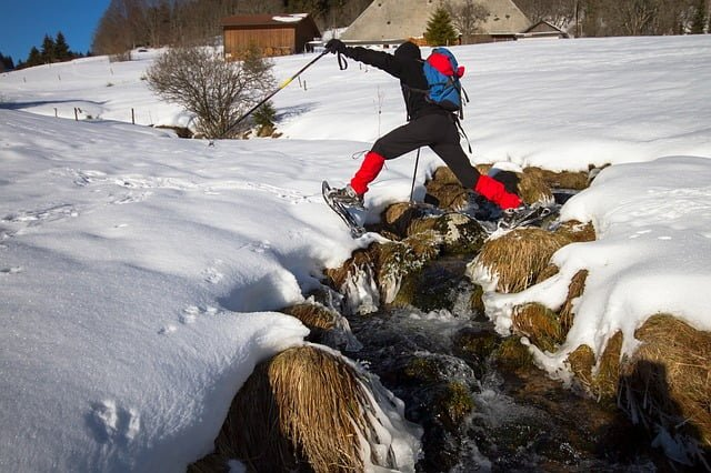 Person jumping over a creek in snow shoes