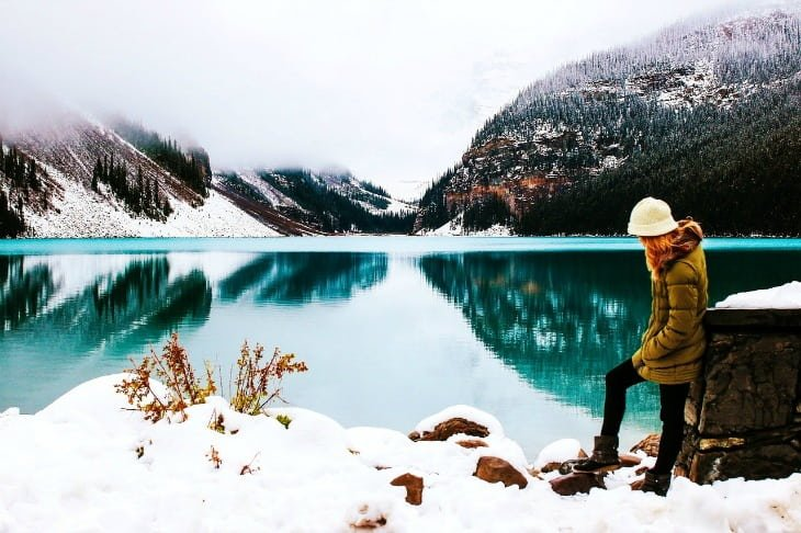 Woman standing by a lake in the winter