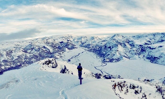 A person looking at snow covered mountains from the top of another mountain