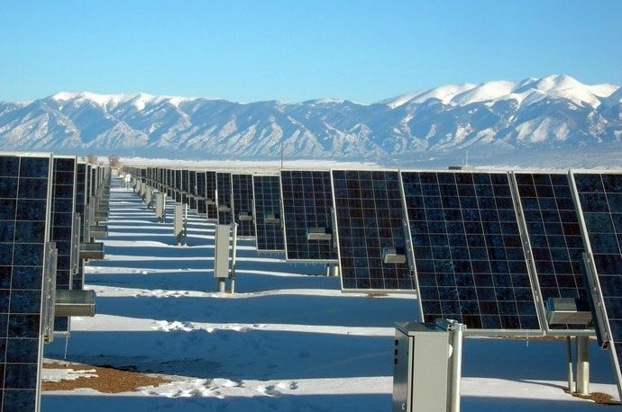 A large number of solar panels next to mountains