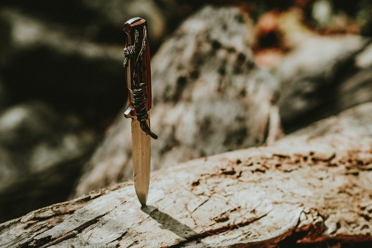 a knife stuck into a piece of wood
