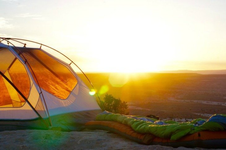 sun rising behind a tent and sleeping bag