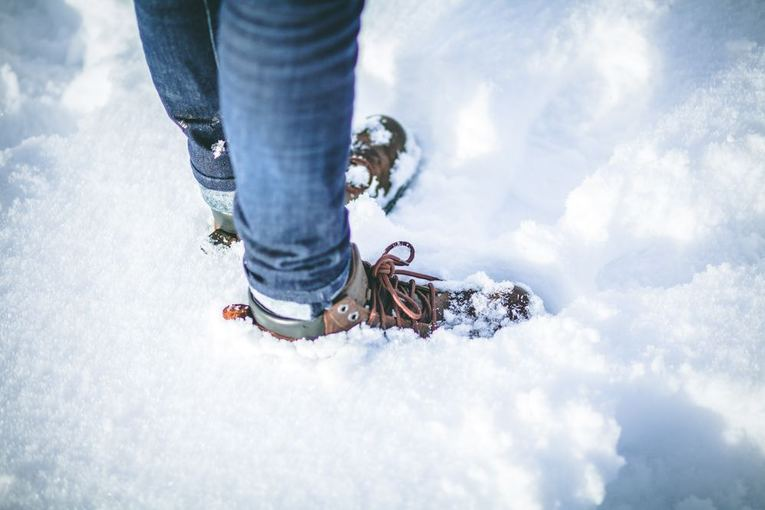 A person standing in snow with boots on