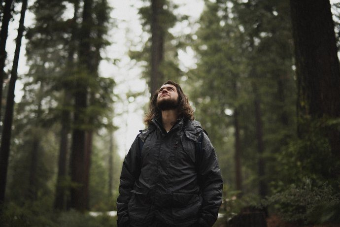 Man in a rain jacket in the forest staring up