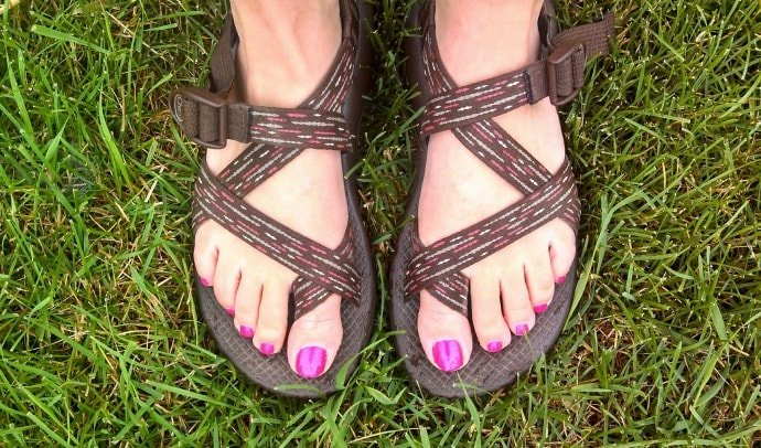 two feet in sandals standing on grass