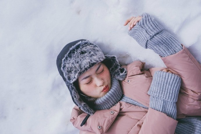 Young lady laying in the snow in snow clothes