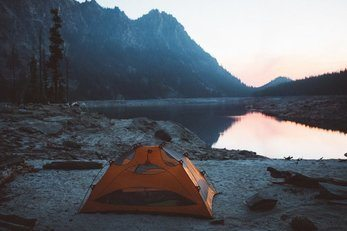 Tent set up next to a lake in the mountains