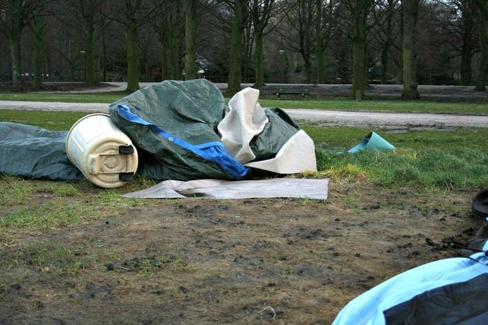 Tent blow over with a trash can laying on it