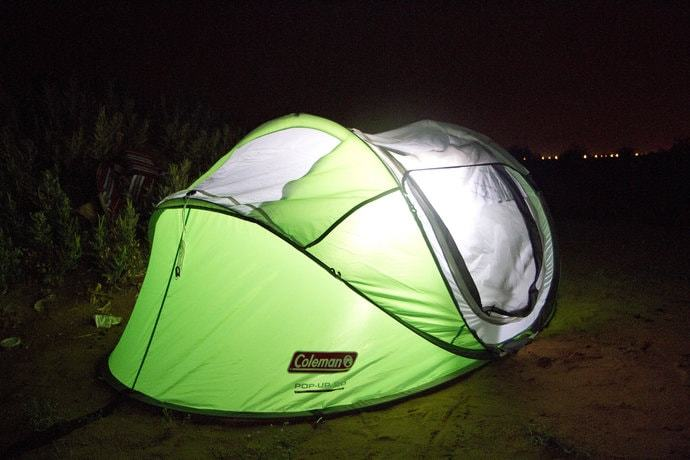 A pop up tent in the dark with a light making the tent glow