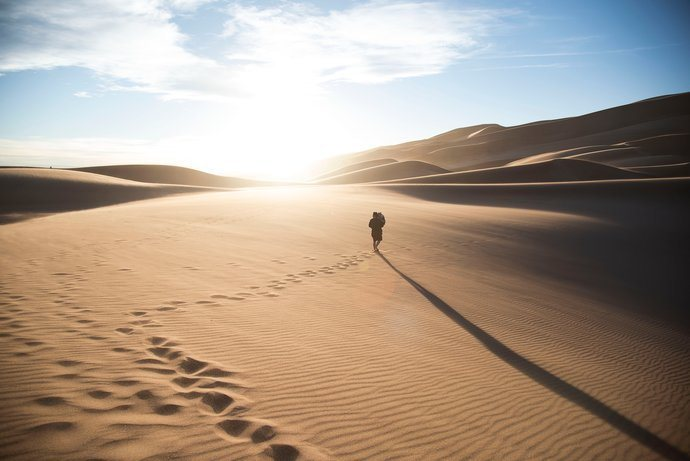 Person walking in a sandy desert on a horizon