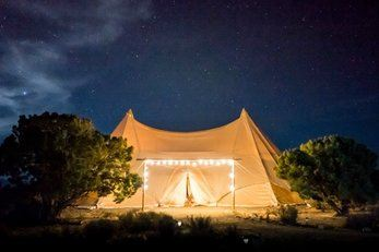 a large tent at night in the woods