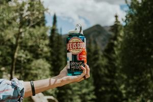 A hand holding a water bottle with mountains in the background