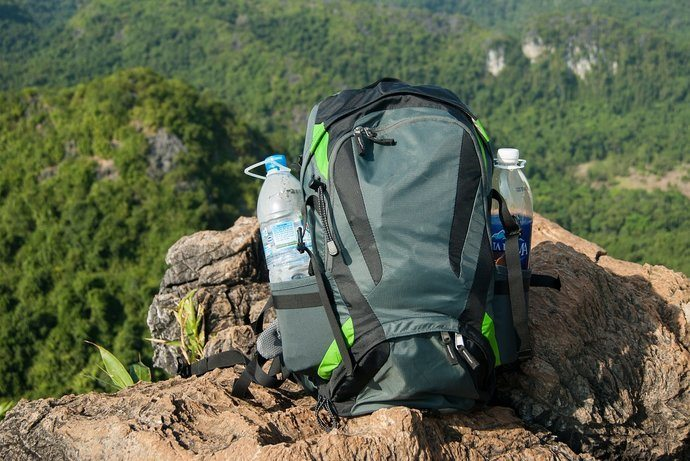 A backpack on a rock with two water bottles on it