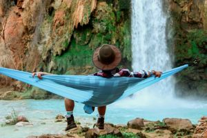 A man with a hat sitting in a hammock looking at a waterfall