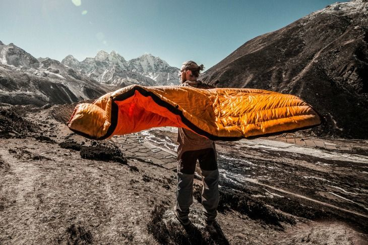 Man holding a sleeping bag in the wind