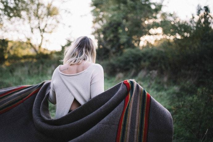 Young lady holding a camping blanket