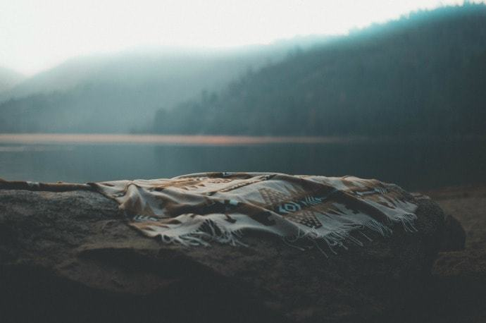 Camping blanket on the ground next to a lake