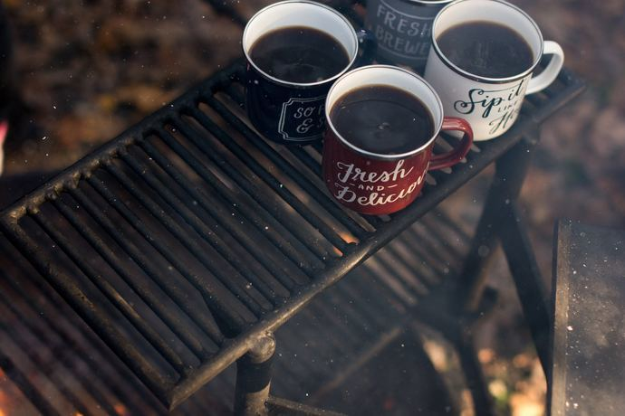 3 cups of coffee sitting on a campfire grill