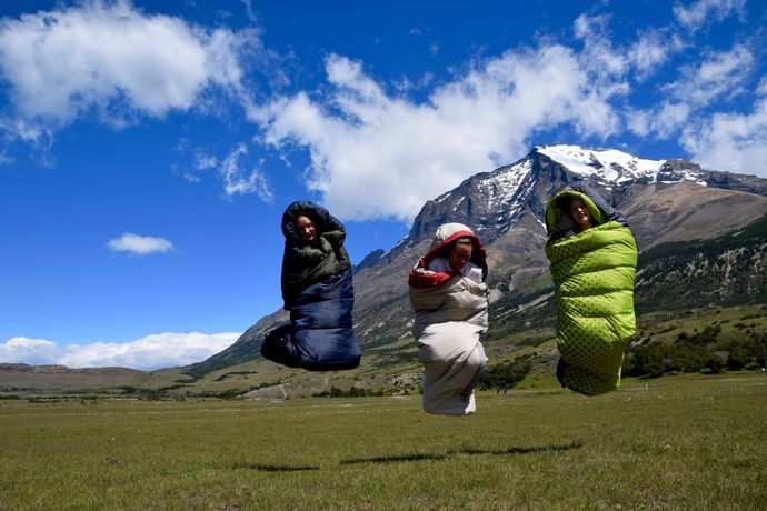 3 people jumping off the ground in a sleeping bag