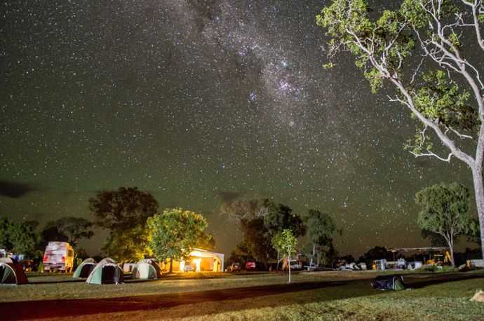 A campground with multiple tents underneath a starry sky