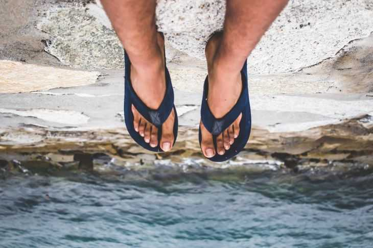 Two feet in flip-flops hanging off a ledge high above the water