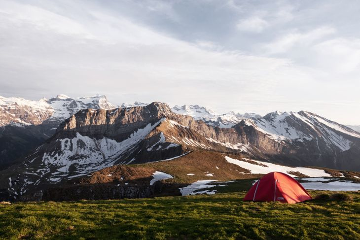 A tent pitched on the plains overlooking the snowy mountainous landscape of Niederbauen-Chulm