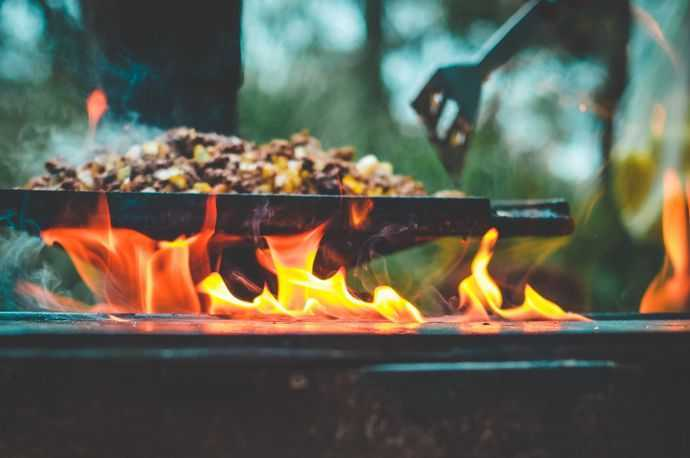 Food being cooked over a propane stove outdoors