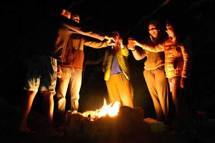 People toasting with plastic cups over a campfire