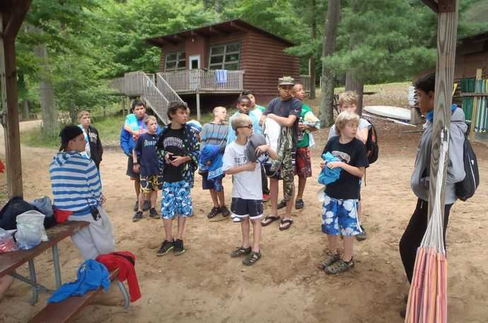 Kids standing in a circle in the woods with a cabin in the background