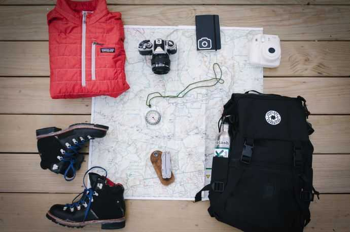 A table with a map, backpack, camera, and boots