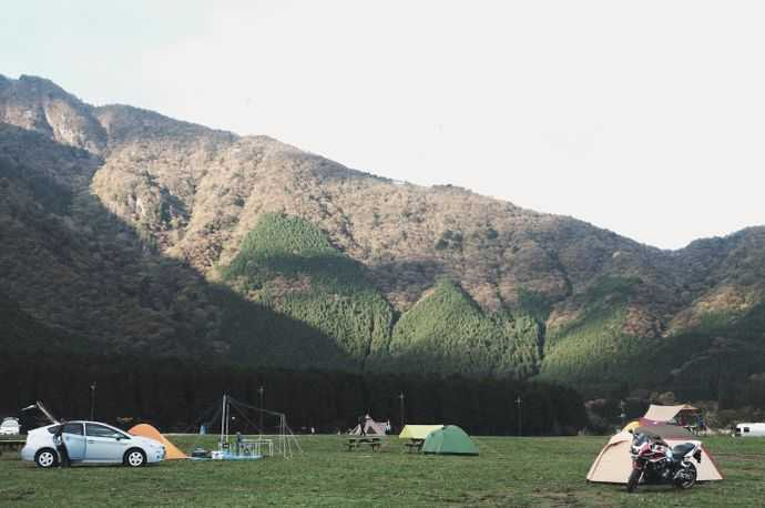 Four tents on a grassy field with a large mountain behind them
