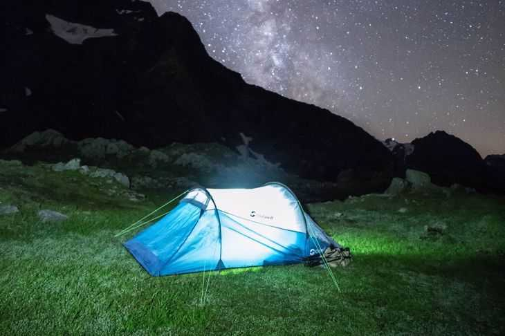 A blue glowing tent in a grass field on a starry evening