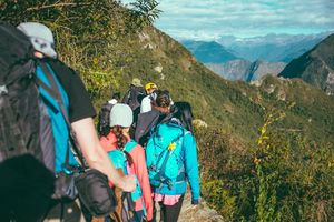 Group of hikers wearing backpacks and hiking gear walking up a mountain