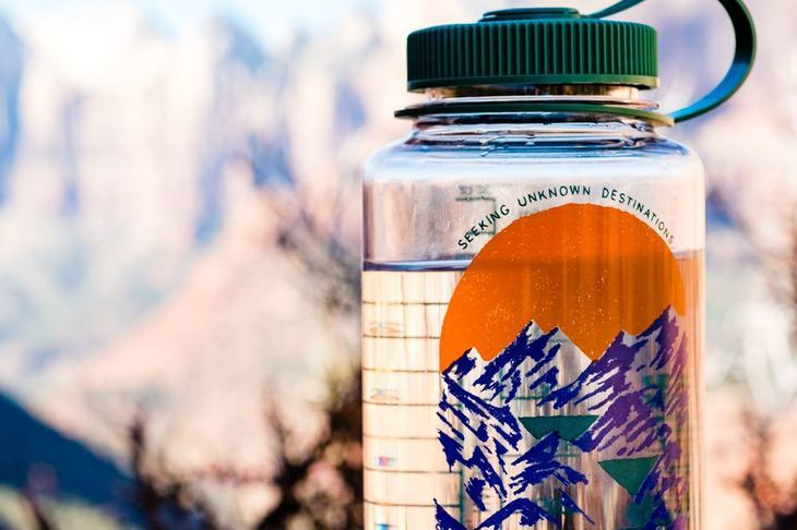 Close up of a water bottle with the wilderness in the background