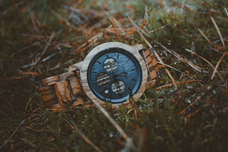A wooden watch laying in a field of grass