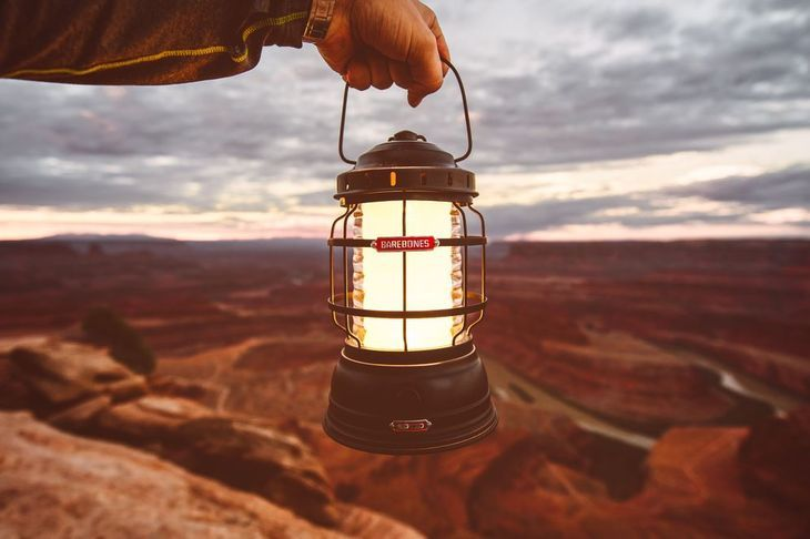 A glowing lantern held up with the desert in the background
