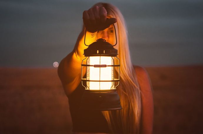Women holding a lantern with the glow lighting her face