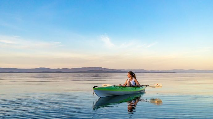 A women on a kayak at sunset