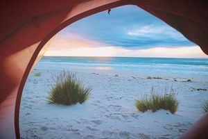 Looking at a the water from the inside of a tent on a sandy beach