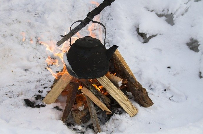 A kettle sitting over a campfire in the snow