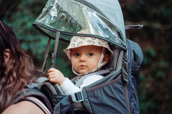 A young baby sitting in a hiking backpack looking at the camera