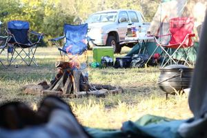 A campsite with chairs around a fire during the day